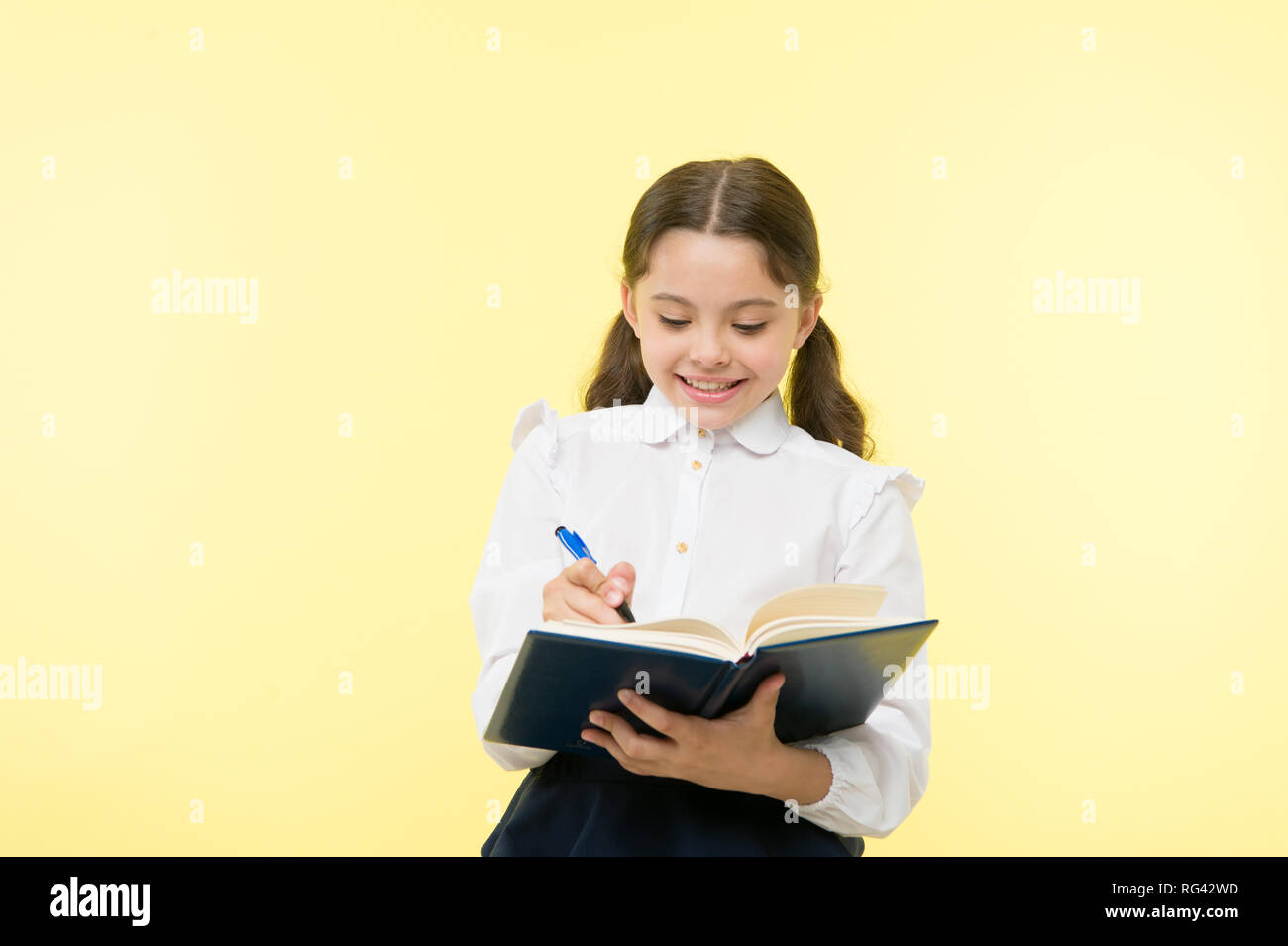 Making notes. Child school uniform kid doing homework. Child girl school uniform clothes hold book and pen. Girl cute write down idea notes. Notes to remember. Write essay or notes. Personal schedule. - Stock Image