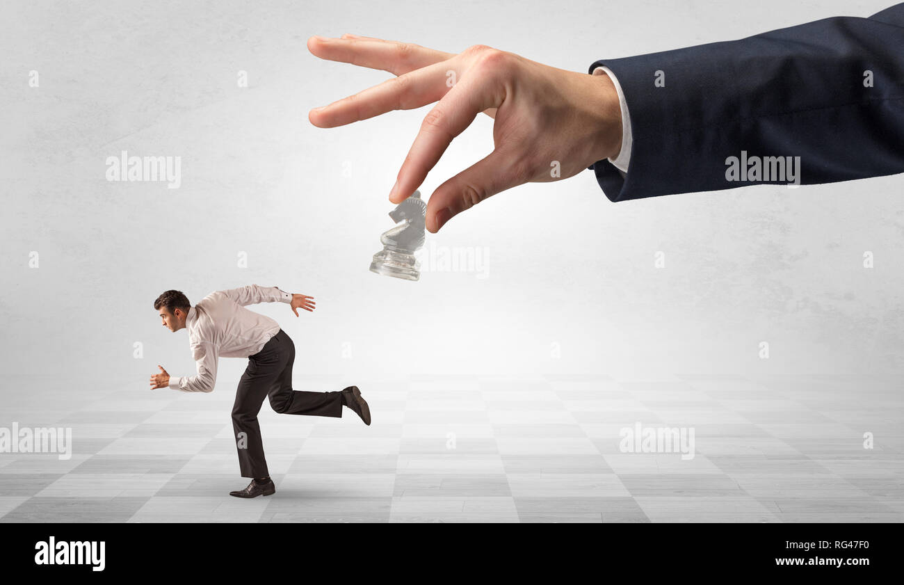 Small frail businessman with suitcase running away from big hand with chessman concept  - Stock Image