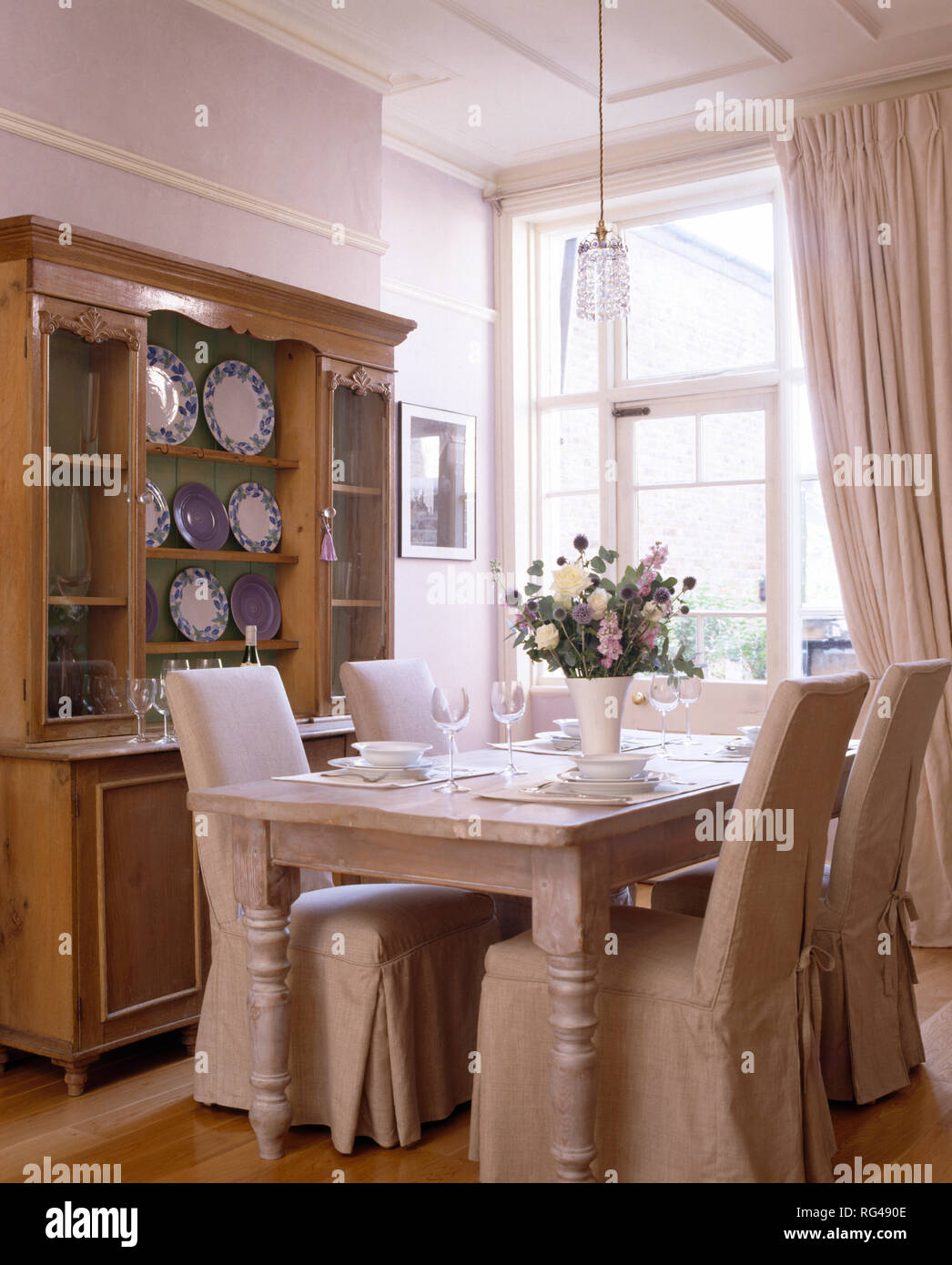 Cream Slip Covers On Chairs At Table In White Dining Room Stock Photo Alamy