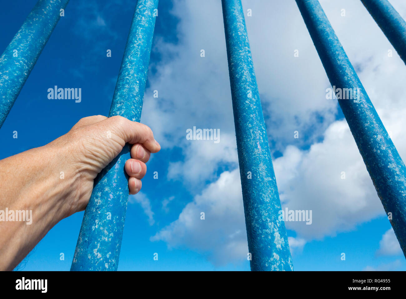 Person behind bars against blue sky. Asylum, border control, illegal immigration, prison... concept. - Stock Image