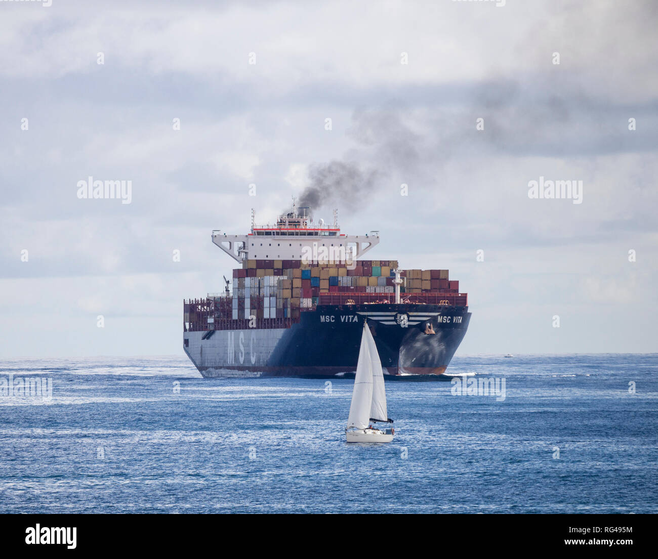Container ship emitting black smoke passing small sailing boats as it enters port. - Stock Image
