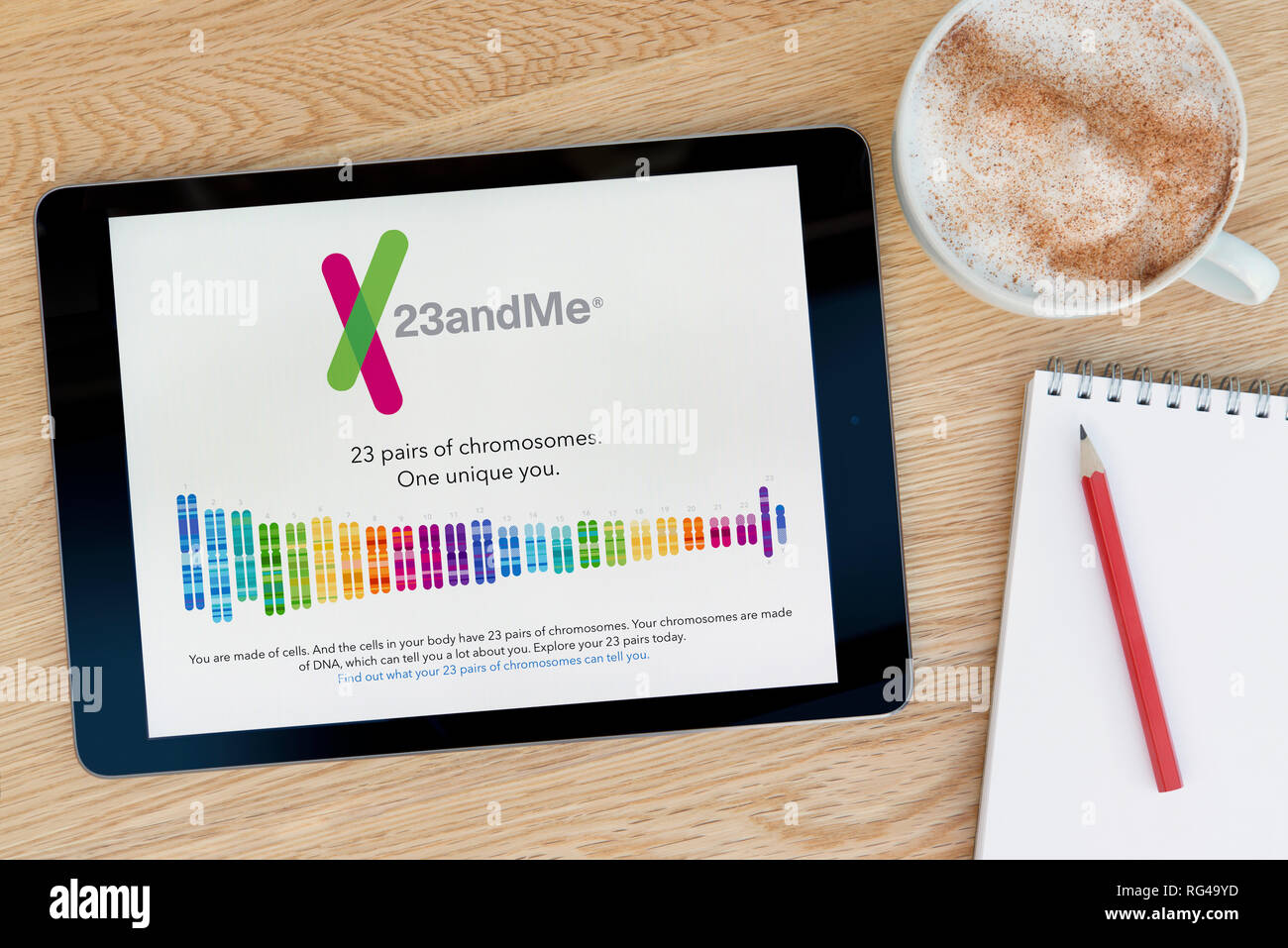The 23andMe website features on an iPad tablet device which rests on a wooden table beside a notepad (Editorial use only). - Stock Image