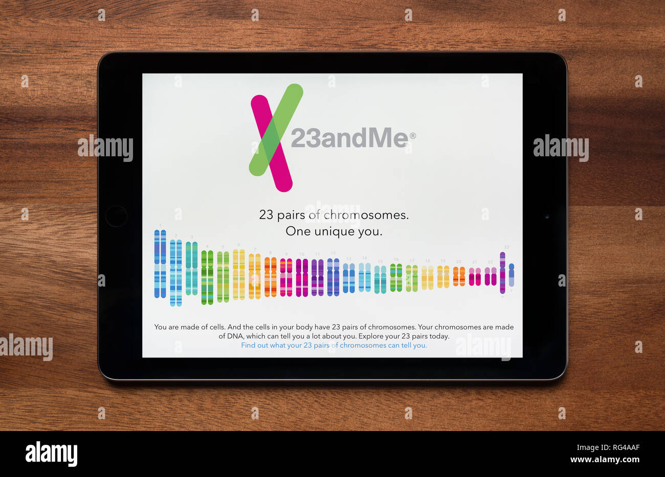 The website of 23andMe is seen on an iPad tablet, which is resting on a wooden table (Editorial use only). - Stock Image