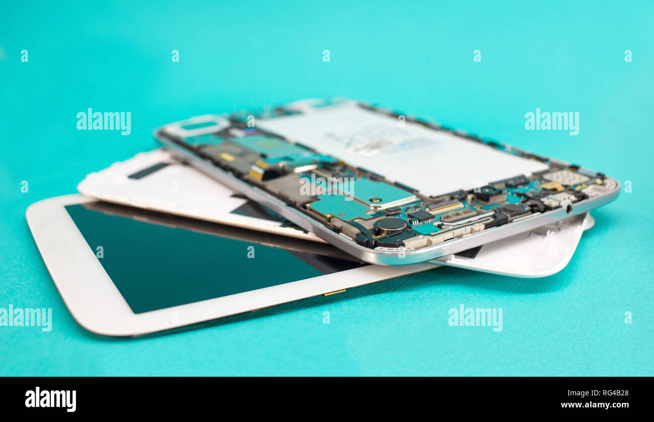 Tablet repair. Close-up disassembled mobile phone parts. Colorful blue background. - Stock Image