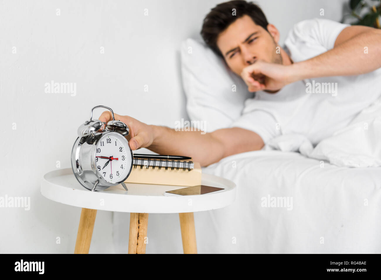 selective focus of yawning man waking up and looking at alarm clock - Stock Image