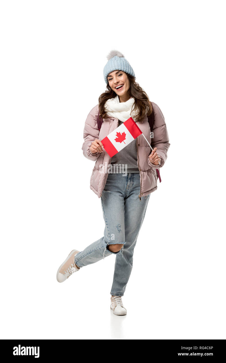 happy female student in winter clothes holding canadian flag isolated on white - Stock Image