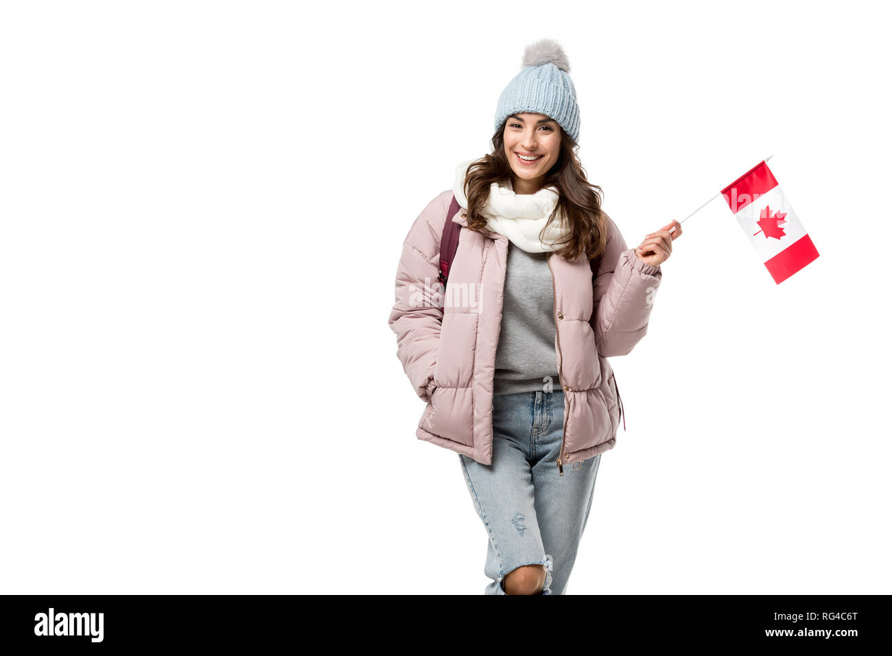 smiling female student in winter clothes holding canadian flag and looking at camera isolated on white - Stock Image
