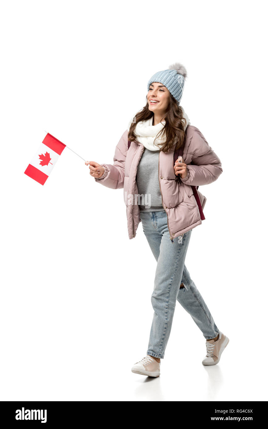 smiling female student in winter clothes with canadian flag isolated on white, travel concept - Stock Image