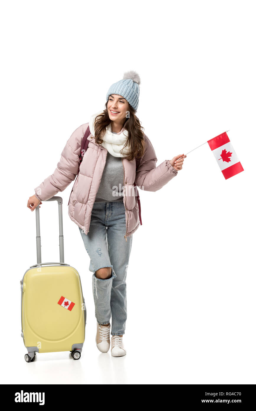 female student in winter clothes with suitcase holding canadian flag isolated on white - Stock Image