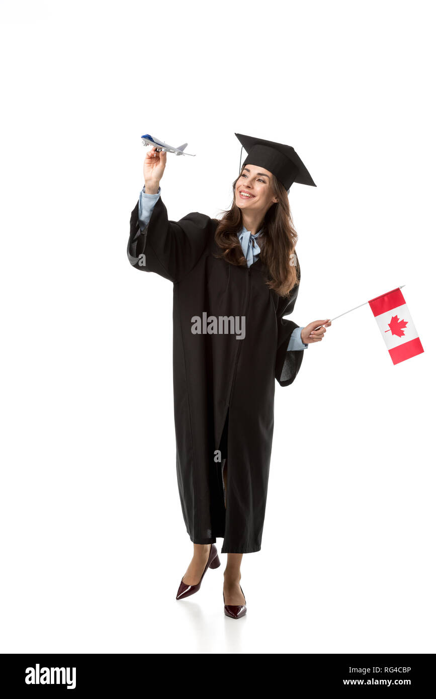 smiling female student in academic gown holding canadian flag and plane model isolated on white, studying abroad concept - Stock Image