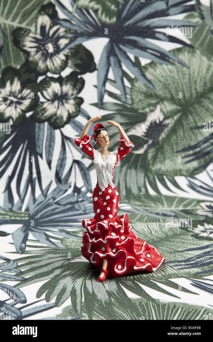 a flamenco dancer figurine on a tropical motif background. Minimal still life color photography - Stock Image