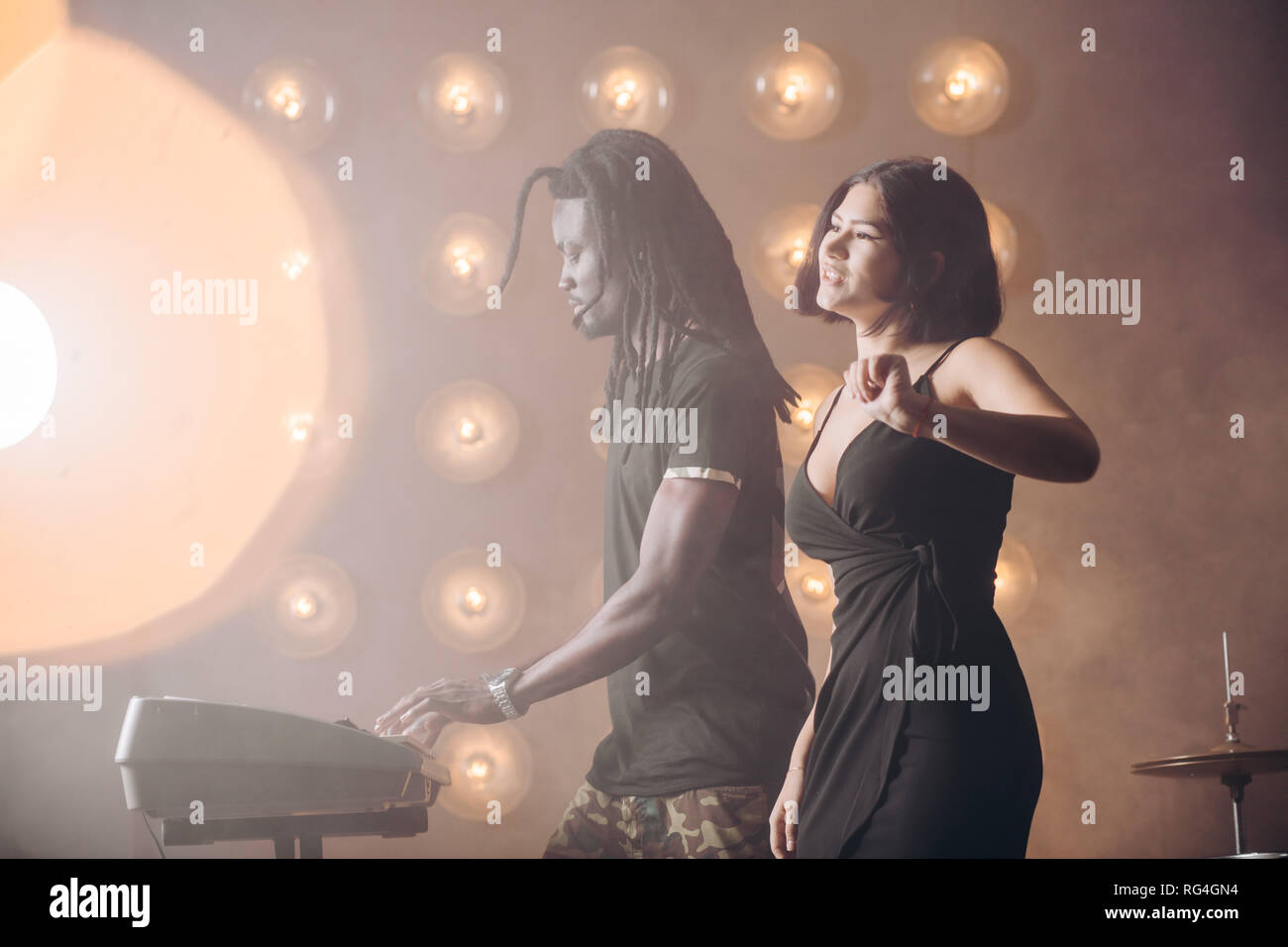 beautiful vocalist girl is singing on the stage. - Stock Image