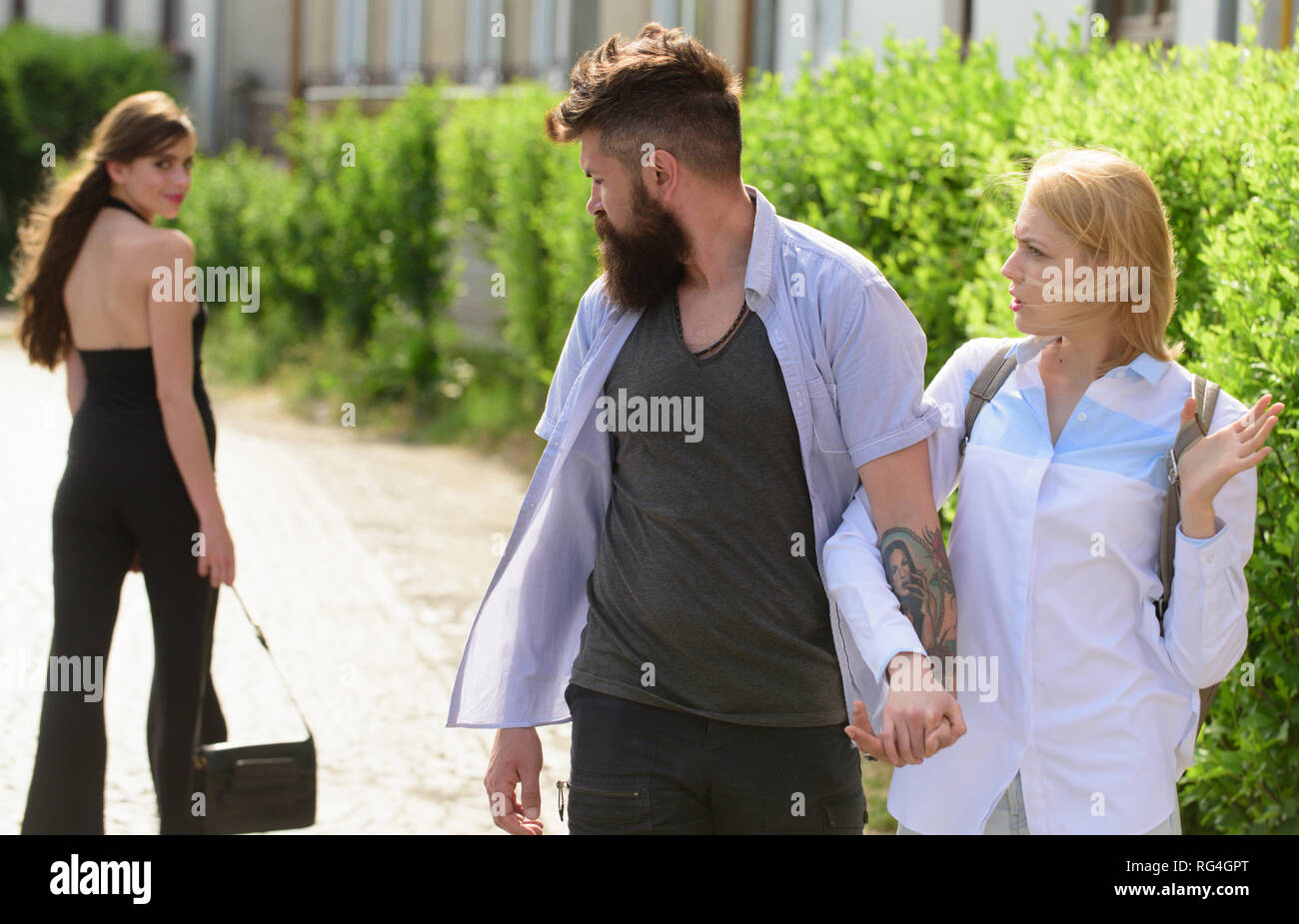 Woman chaser. Man cheating his wife or girlfriend. Love triangle and threesome. Bearded man looking at other girl. Hipster choosing between two women - Stock Image