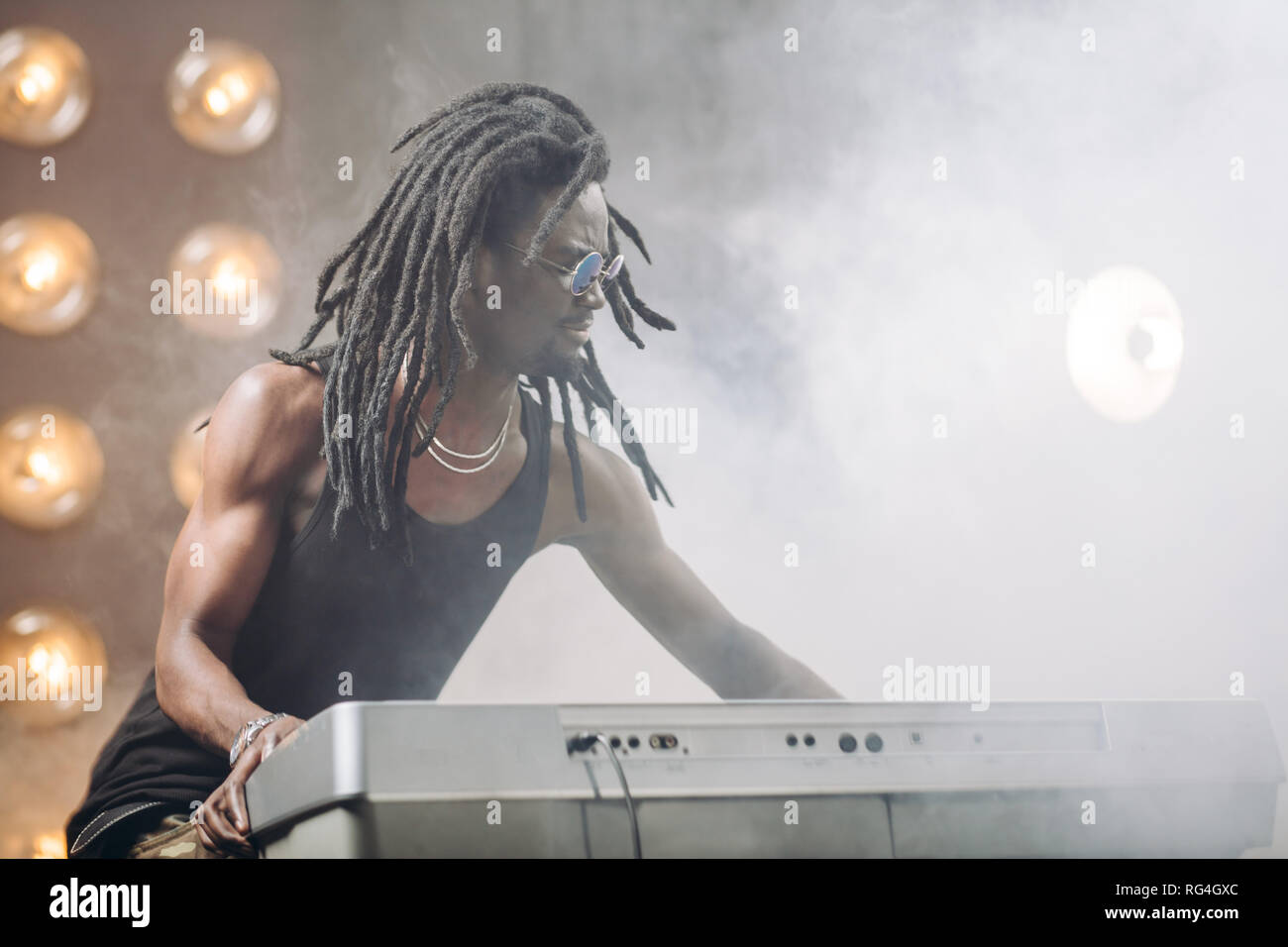 talented man is playing the synthesizer on the smoky stage - Stock Image