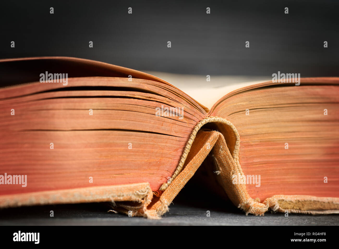 Open ancient book on wooden table close up. Selective focus - Stock Image
