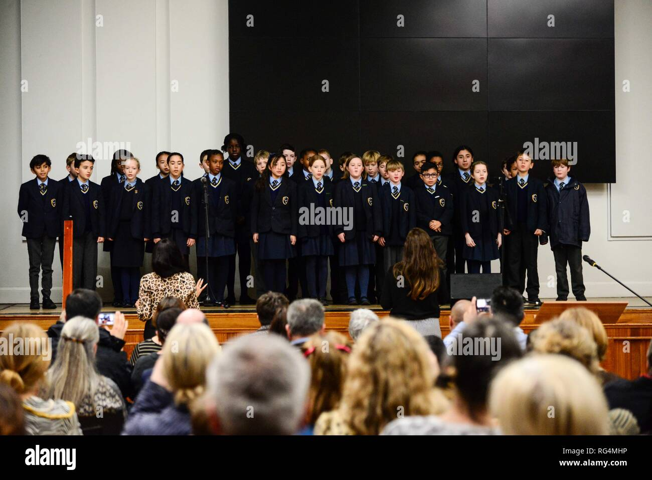 "London,UK. 27th Jan 2019.  Corpus Christi school choir perform  at a Holocaust Memorial Day ceremony held at Lambeth Assembly Hall.The theme for 2019 set by the Holocaust Memorial Day Trust is ""Torn from Home"".  Lambeth Council has agreed to resettle 28 families from the camps around Syria as well as  from other countries in the region. 25 families have arrived since April 2016. Credit: Claire Doherty/Alamy Live News Stock Photo"