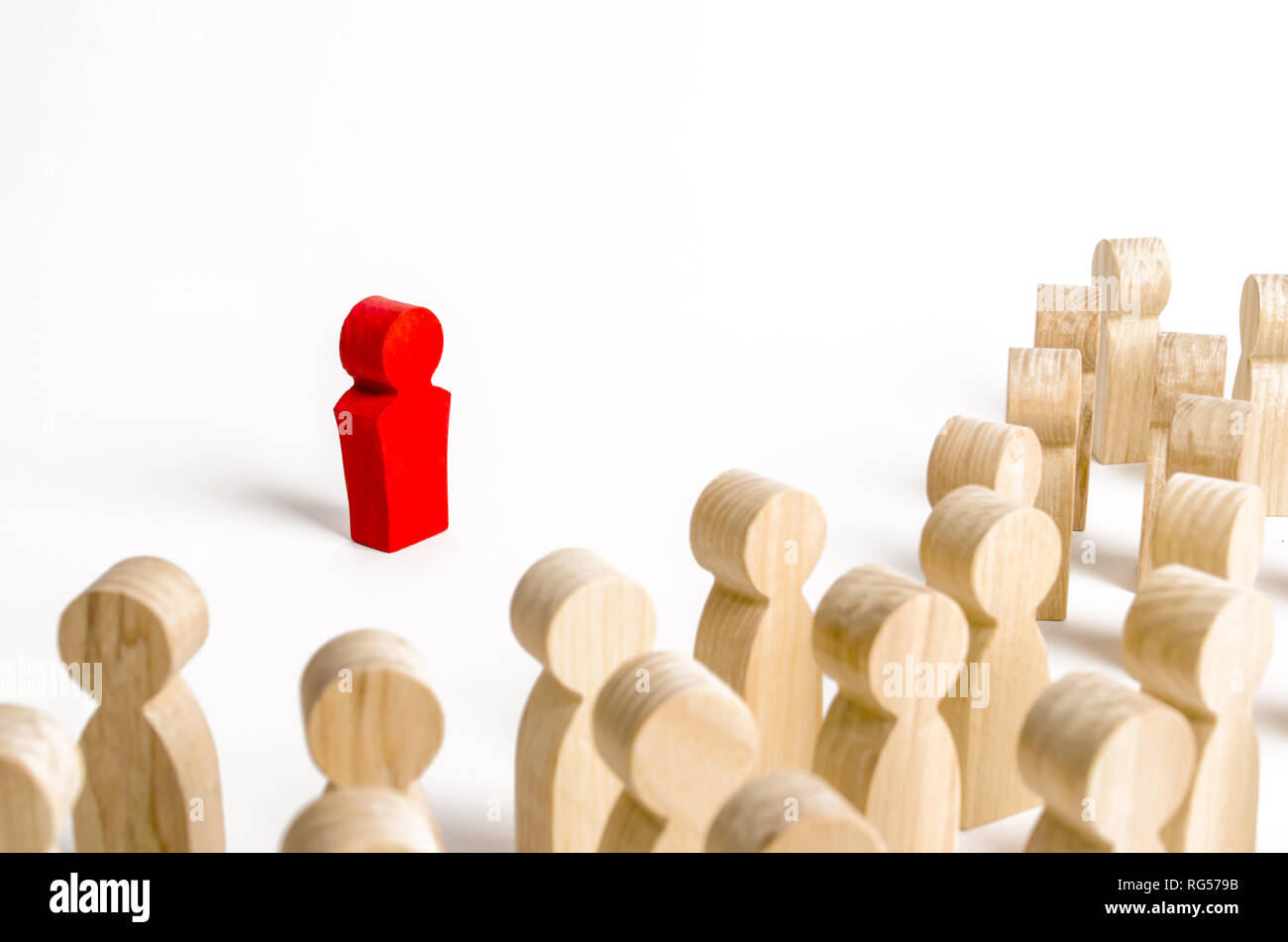 Red figurine of a man in the spotlight of a crowd of people. Leader, leadership and initiator of action. work or business organization. team building. - Stock Image