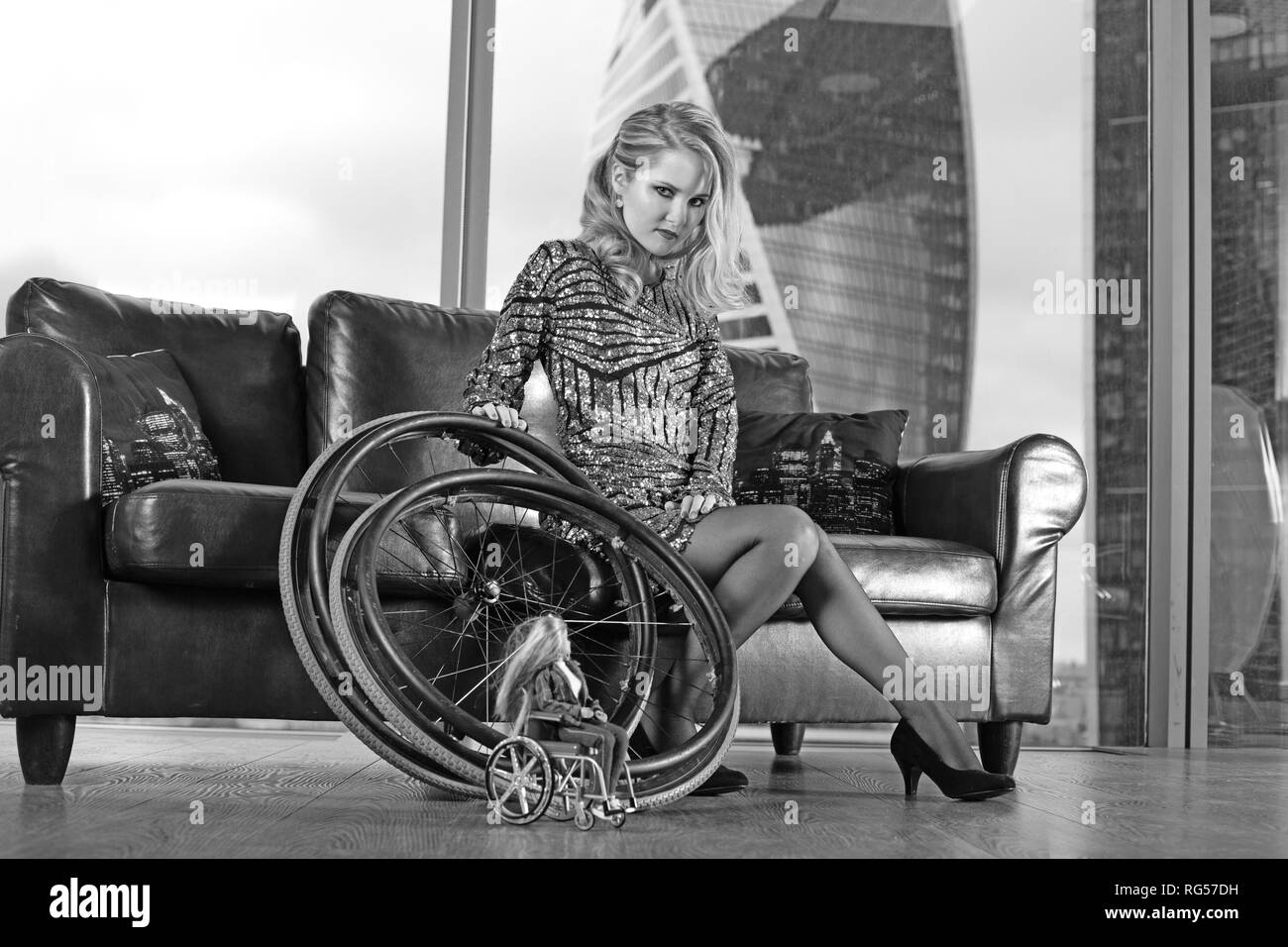 A beautiful young blonde girl with a disability, posing on a leather sofa against the background of a panoramic window - Stock Image
