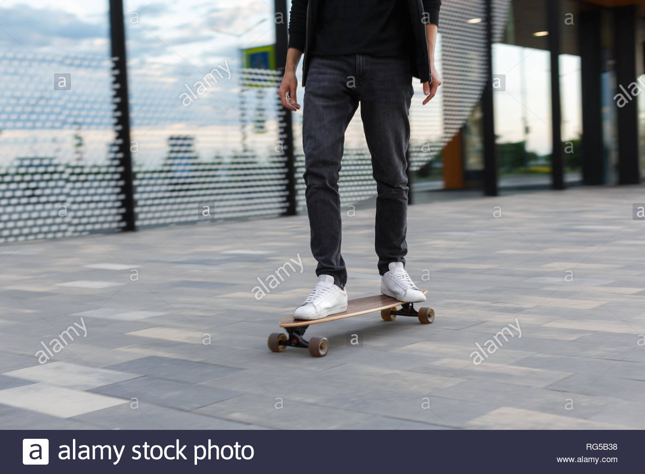 Close up shot of young man in black jeans and white sneakers riding a longboard to the left in urban area hurry on a date in motion wooden longboard