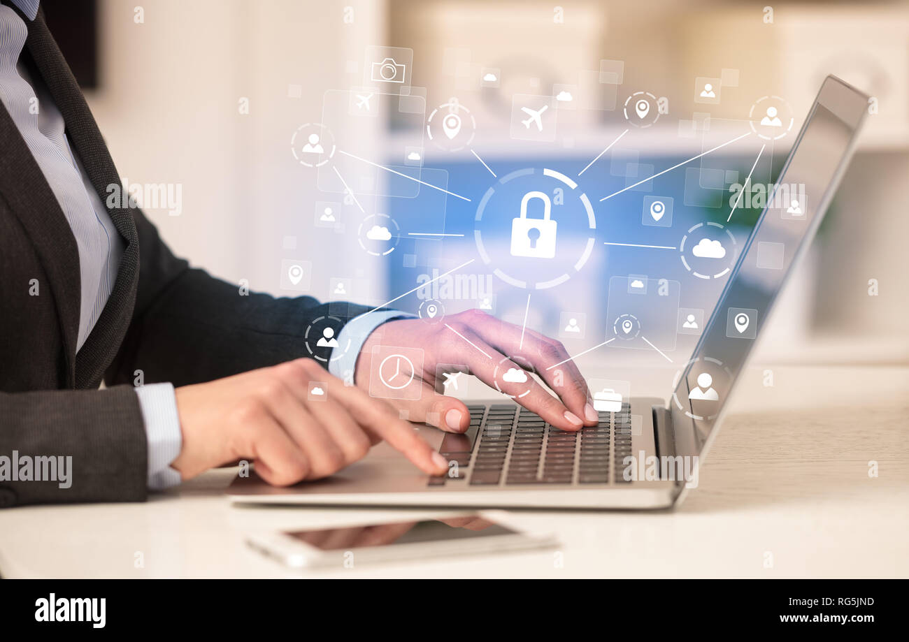 Business woman below chest working on laptop in a cozy homey environment with secured connection concept  - Stock Image