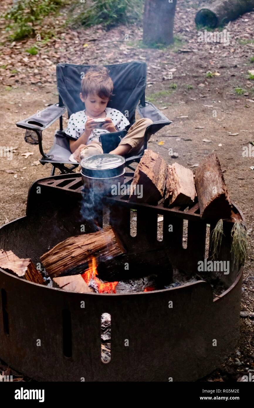 A young girl sits near a campfire, Fern flat campsite area, Eungella National Park, Queensland, Australia Stock Photo
