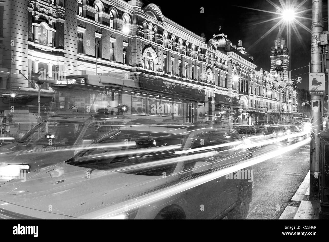 Flinders Street Station is a famous landmark and tourist attraction in Melbourne, Victoria, Australia. Shown with tram and vehicle traffic on Flinders Stock Photo
