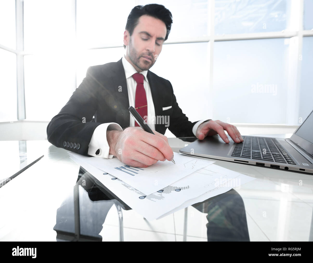 businessman uses a laptop to check financial data - Stock Image