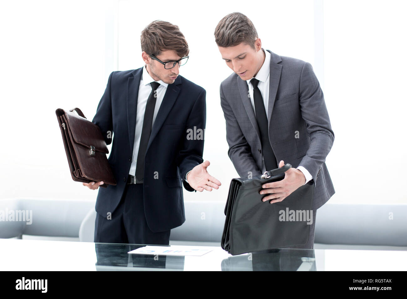 two business people discuss financial documents. - Stock Image