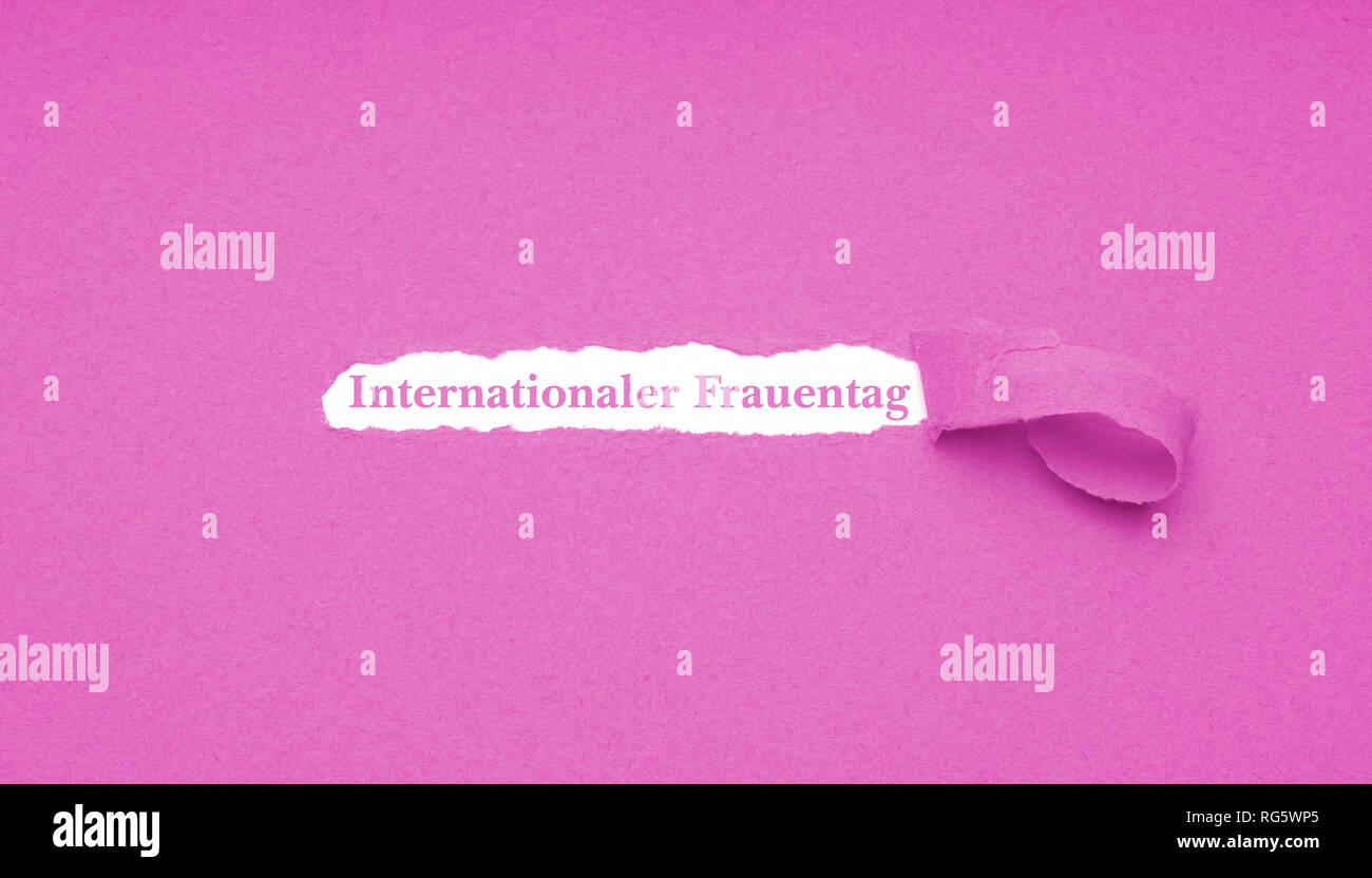 Internationaler Frauentag is German for International Women's Day which is celebrated on March 8 - text revealed by hole torn in pink paper background - Stock Image
