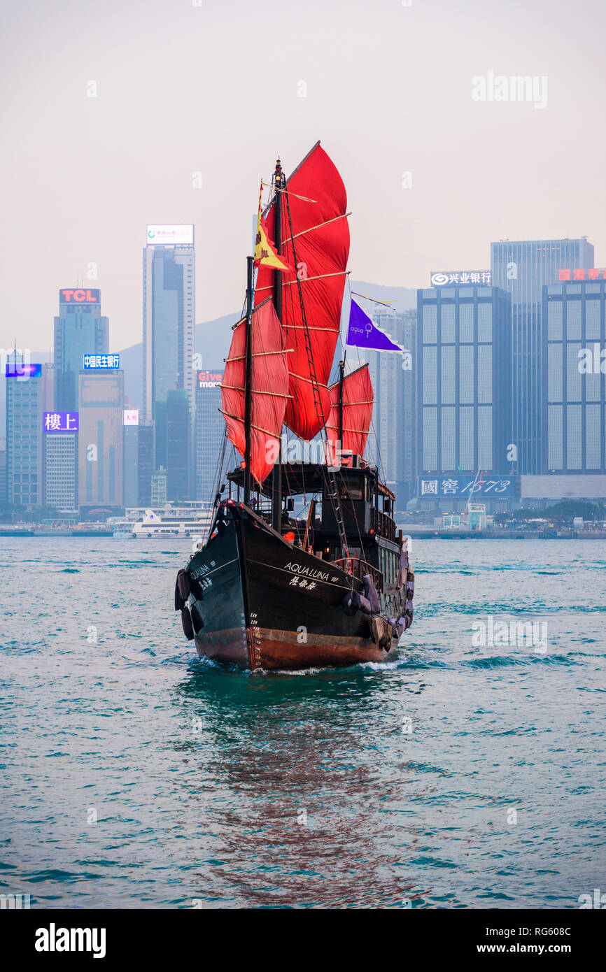 Sunset sailing of the Aqualuna junk tourist boat, Victoria Harbour, Hong Kong - Stock Image