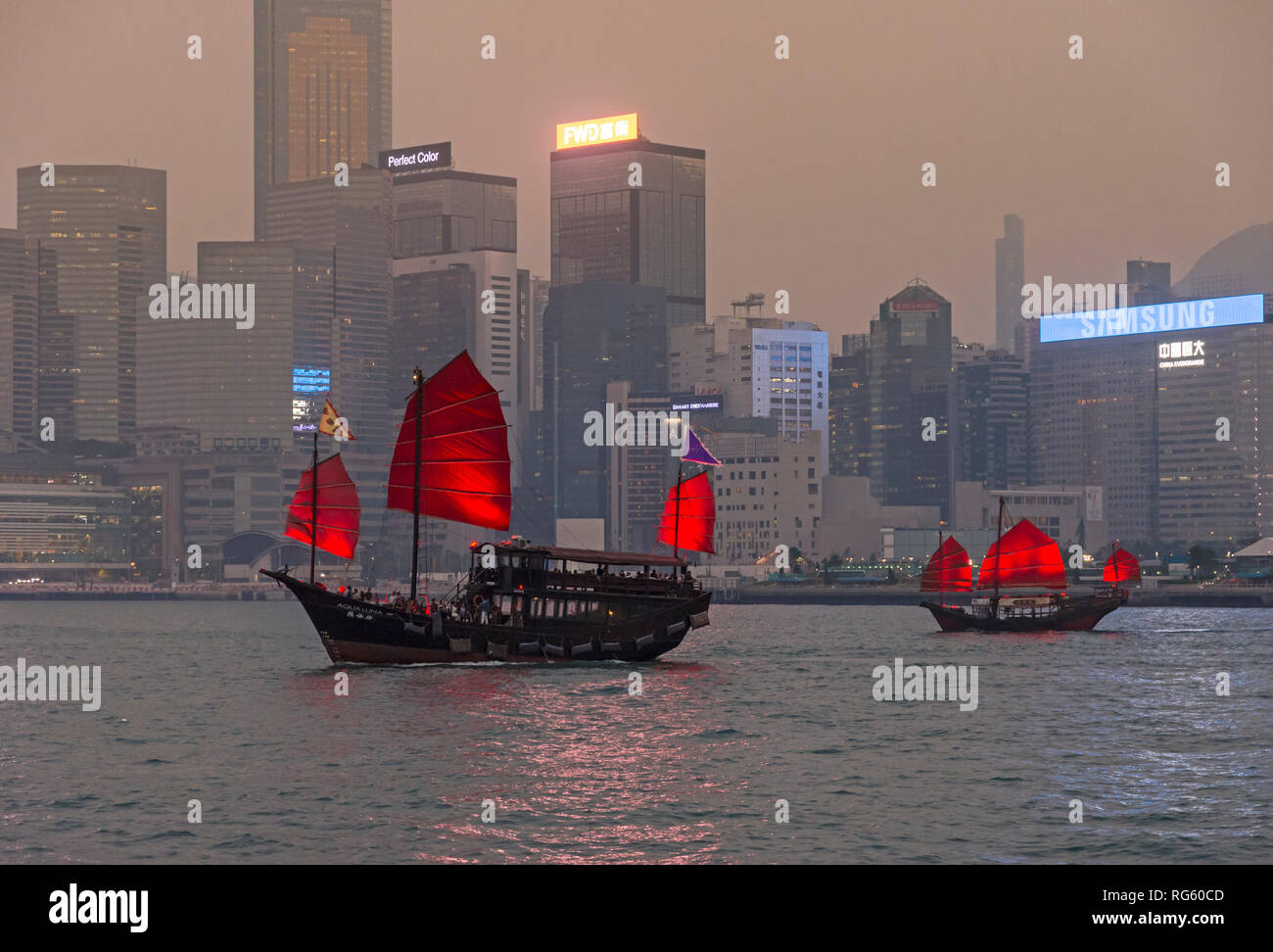 Aqualuna and Dukling junk tourist boats on their sunset sailing, Victoria Harbour, Hong Kong - Stock Image