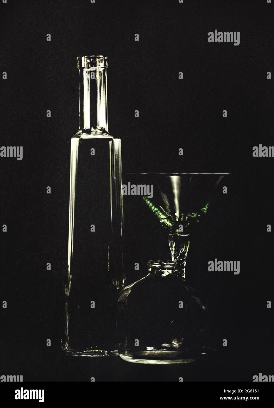 Empty bottles and a cocktail glass, poison, murder concept. Backlit so black background, artistic texture applied. - Stock Image