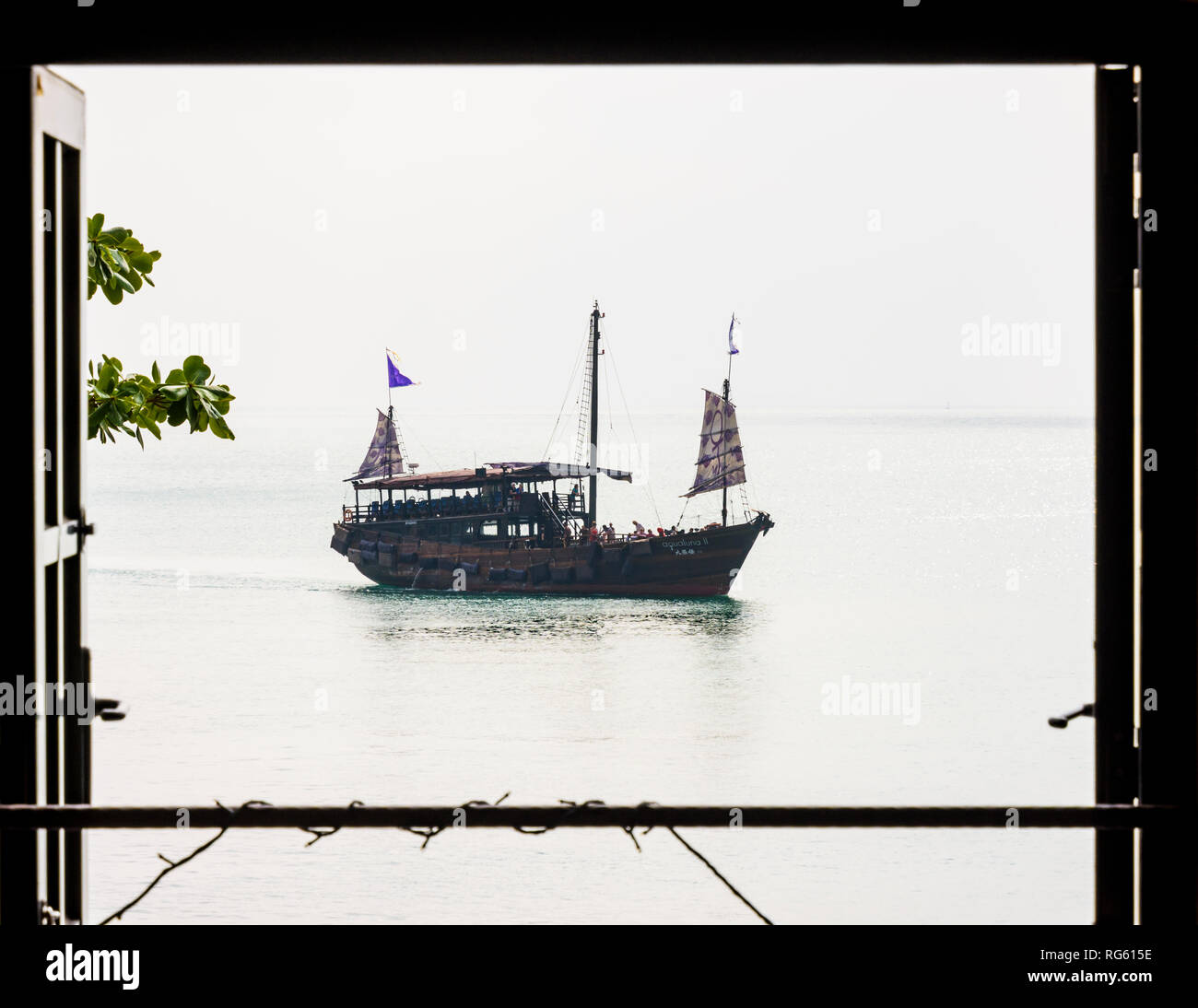 Framed view of a hazy day arrival of the Aqua Luna II junk in Stanley Bay, Hong Kong - Stock Image
