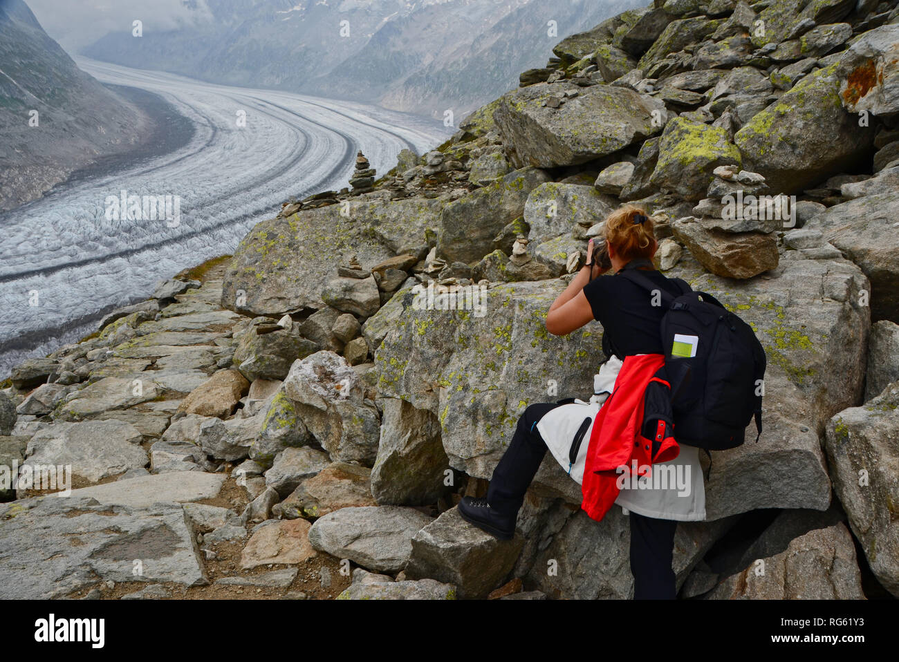 Woman taking a photo of the Great Aletsch Glacier, Valais, Switzerland Stock Photo