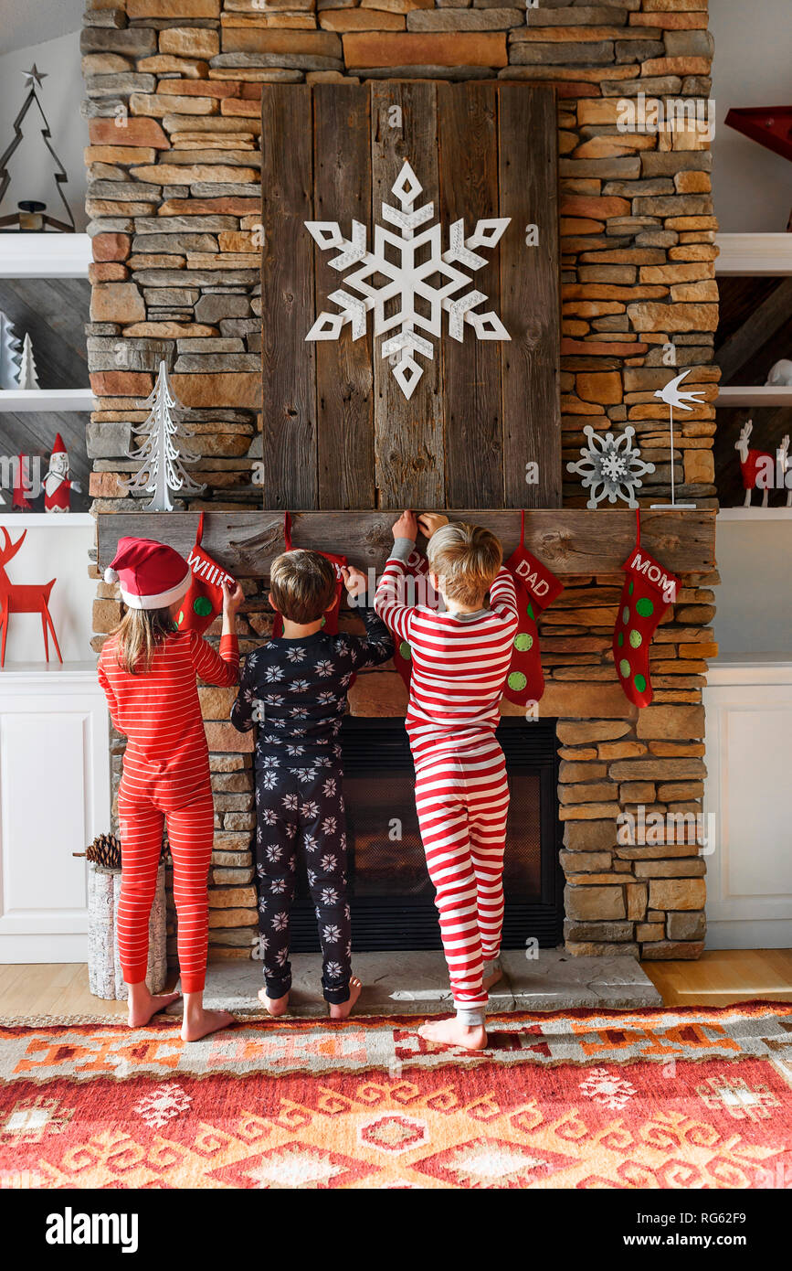 Three children hanging up Christmas stockings on a fireplace ...