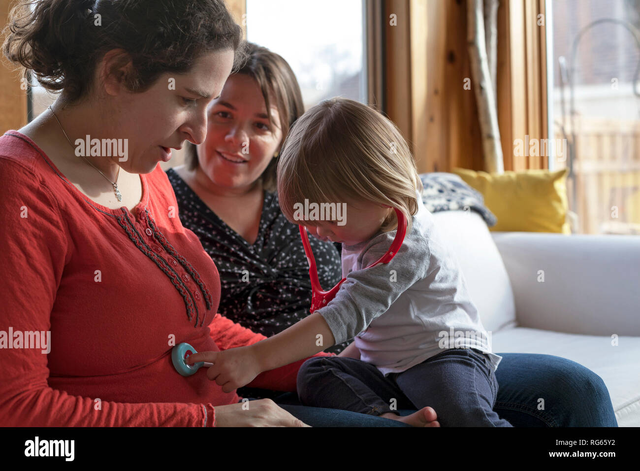 A toddler uses a stethoscope on a pregnant woman. - Stock Image