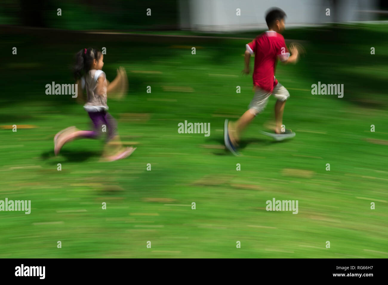 Motion blur of child running in park - Stock Image