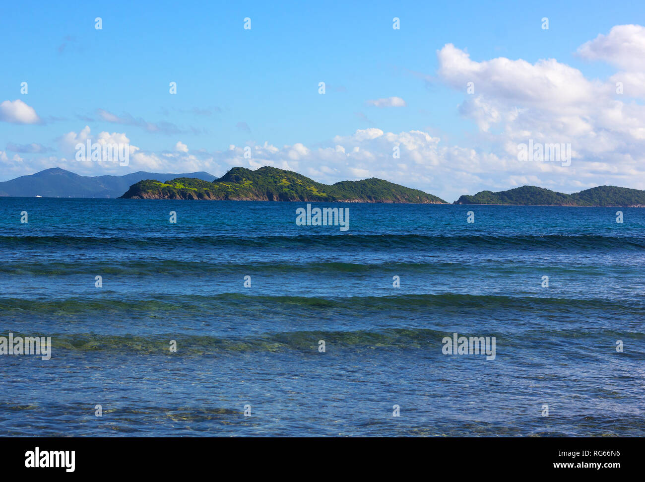 Gentle waves rolling onto a shore of St. Thomas island beach in winter. Warm welcoming waters of Caribbean Sea with a view on mountainous islands on h Stock Photo