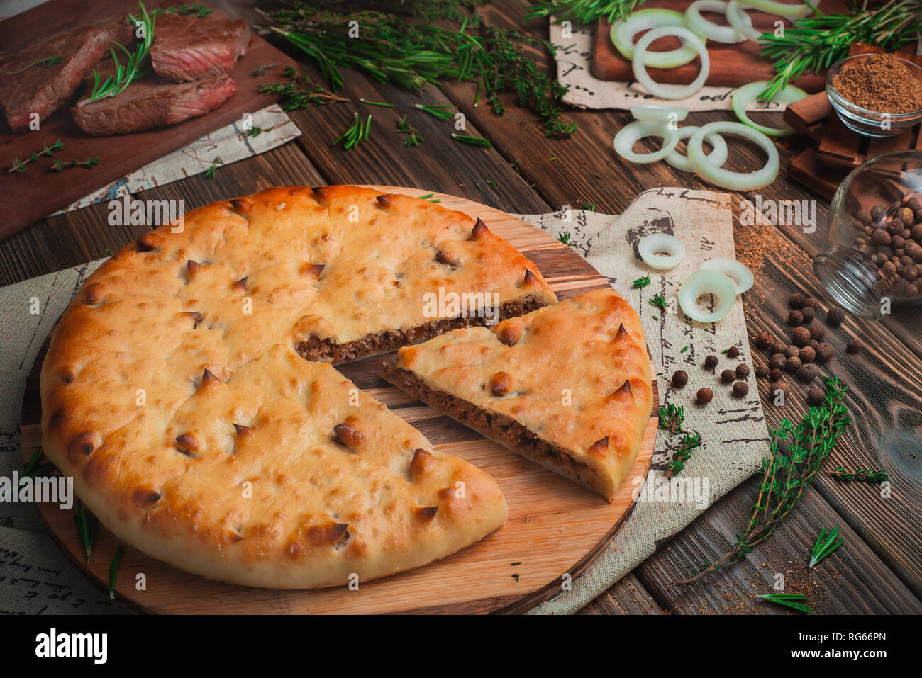 Ossetian meat pie with beef on a wooden background with ingredients. Traditional baking concept with copy space - Stock Image
