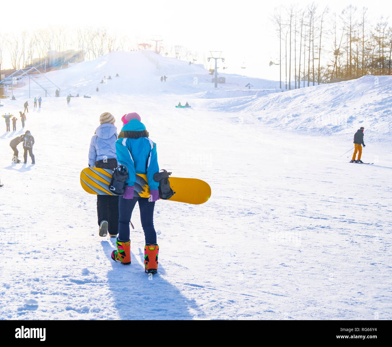 Young girls in special colored suits for winter fun and winter sports climb the hill to learn how to snowboard on a sunny day. - Stock Image