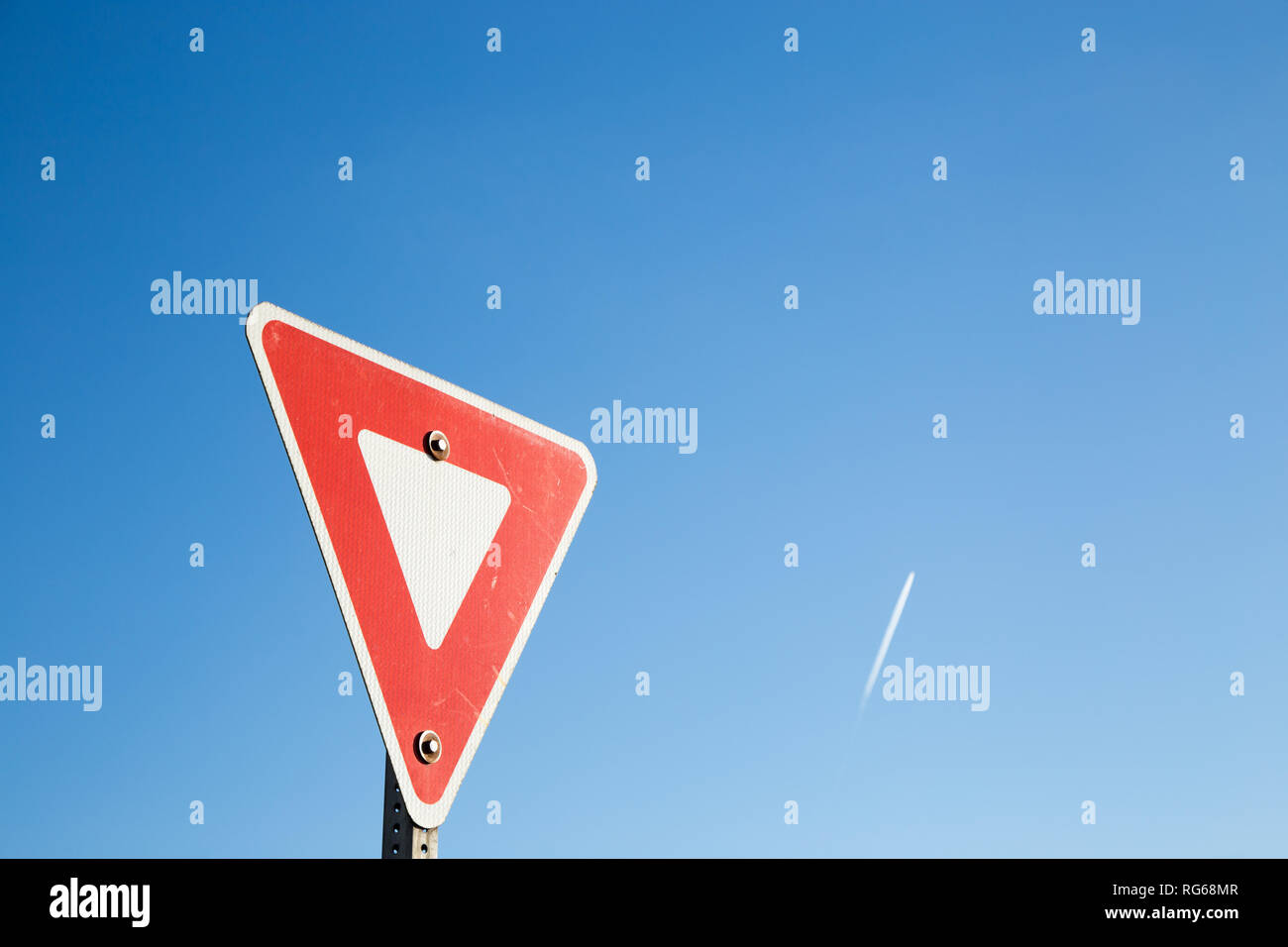 Yield sign against a blue sky with a contrail. - Stock Image