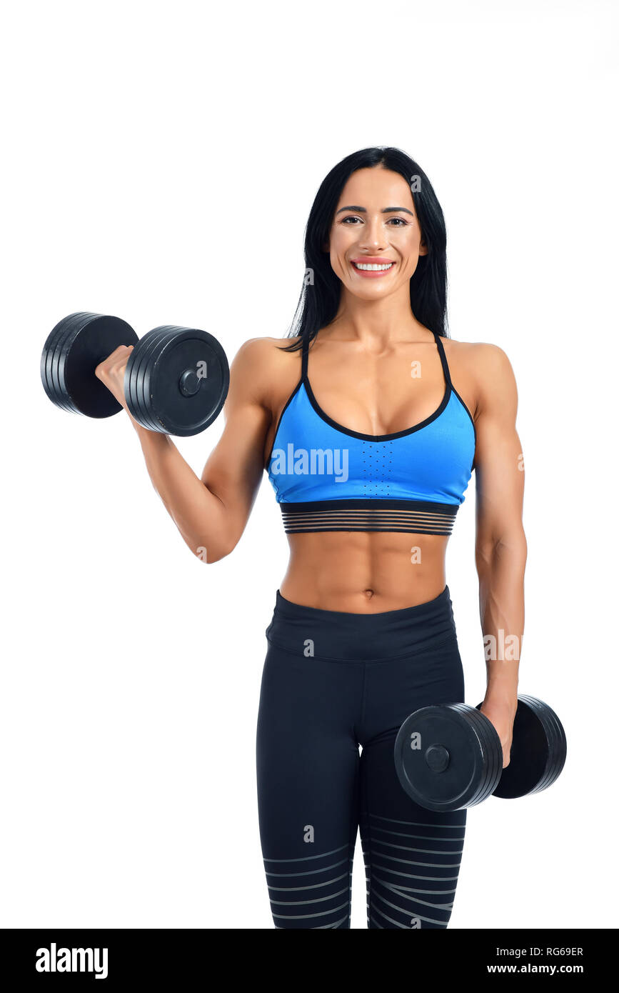 Portrait of very strong and young woman working regularly in gym under her body. Smiling athlete in sportswear holding dumbbells and demonstrating power. Personal trainer offering help for everyone. - Stock Image