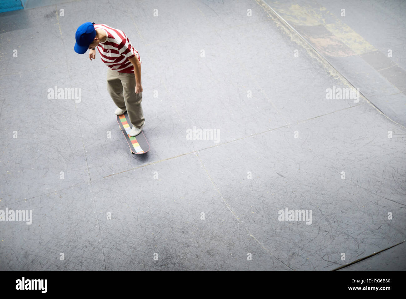 View of young man in casualwear standing on skateboard and moving along special flat area for acrtivities - Stock Image