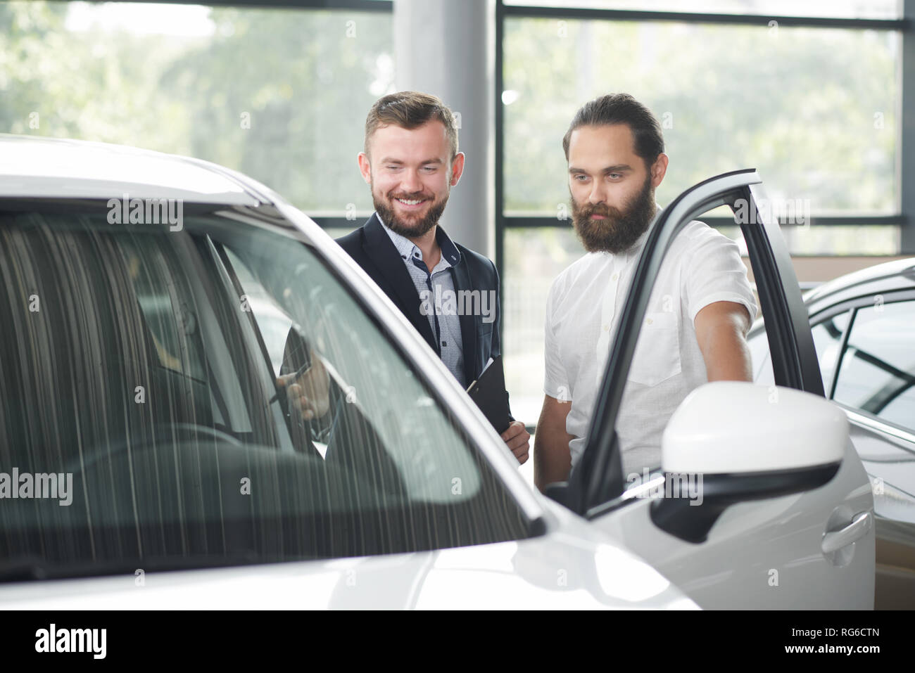 Car dealer showing car to customer. Brutal bearded man in white shirt looking at car, observing. Men standing near white automobile. Client looking for vehicle in car dealership. - Stock Image