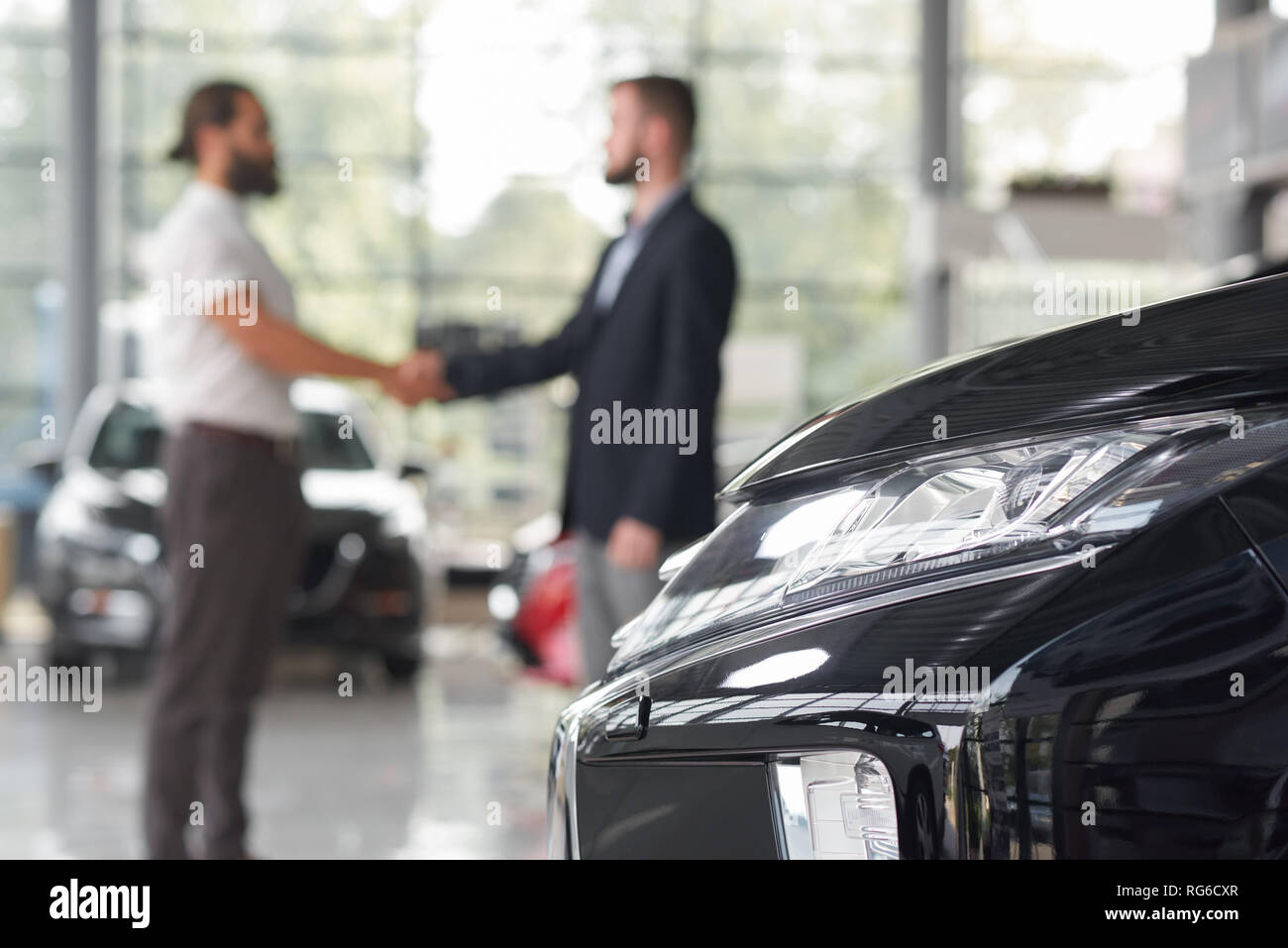 Automobile headlight and men standing behind. Car dealer and client of car dealership shaking hands. Manager and customer making deal on purchasing vehicle. Modern auto showroom. - Stock Image