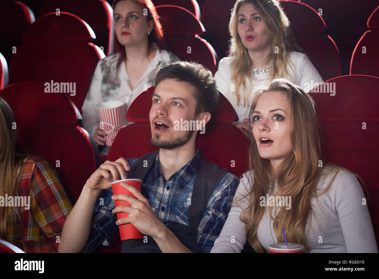View of shocked couple looking at screen in cinema theater with opened mouth. pretty blonde girl in gray and handsome man enjoying scary movie. Concept of friends and free time. Stock Photo