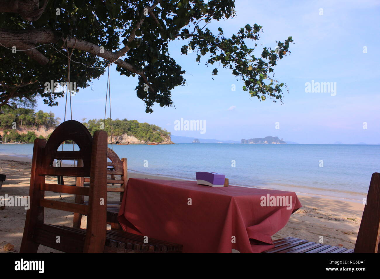 Tisch und Stühle am Strand einer thailändischen Insel mit Ausblick aufs Meer und die umgebenden Inseln - Stock Image