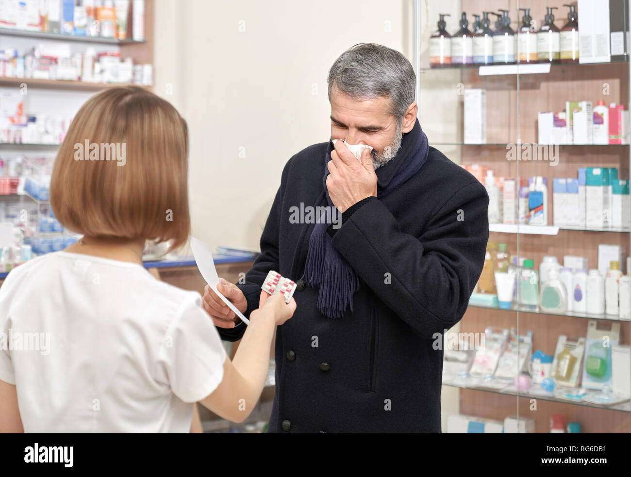 Sick man with flu consulting with pharmacist about medicaments. Female specialist in white coat offering blister pack of helpful pills. Man having blocked nose, blowing nose with tissue, coughing. - Stock Image