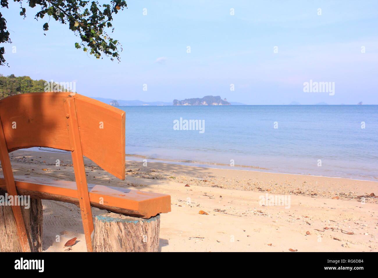 Holzbank am Strand einer thailändischen Insel mit Ausblick aufs Meer und die umgebenden Inseln - Stock Image