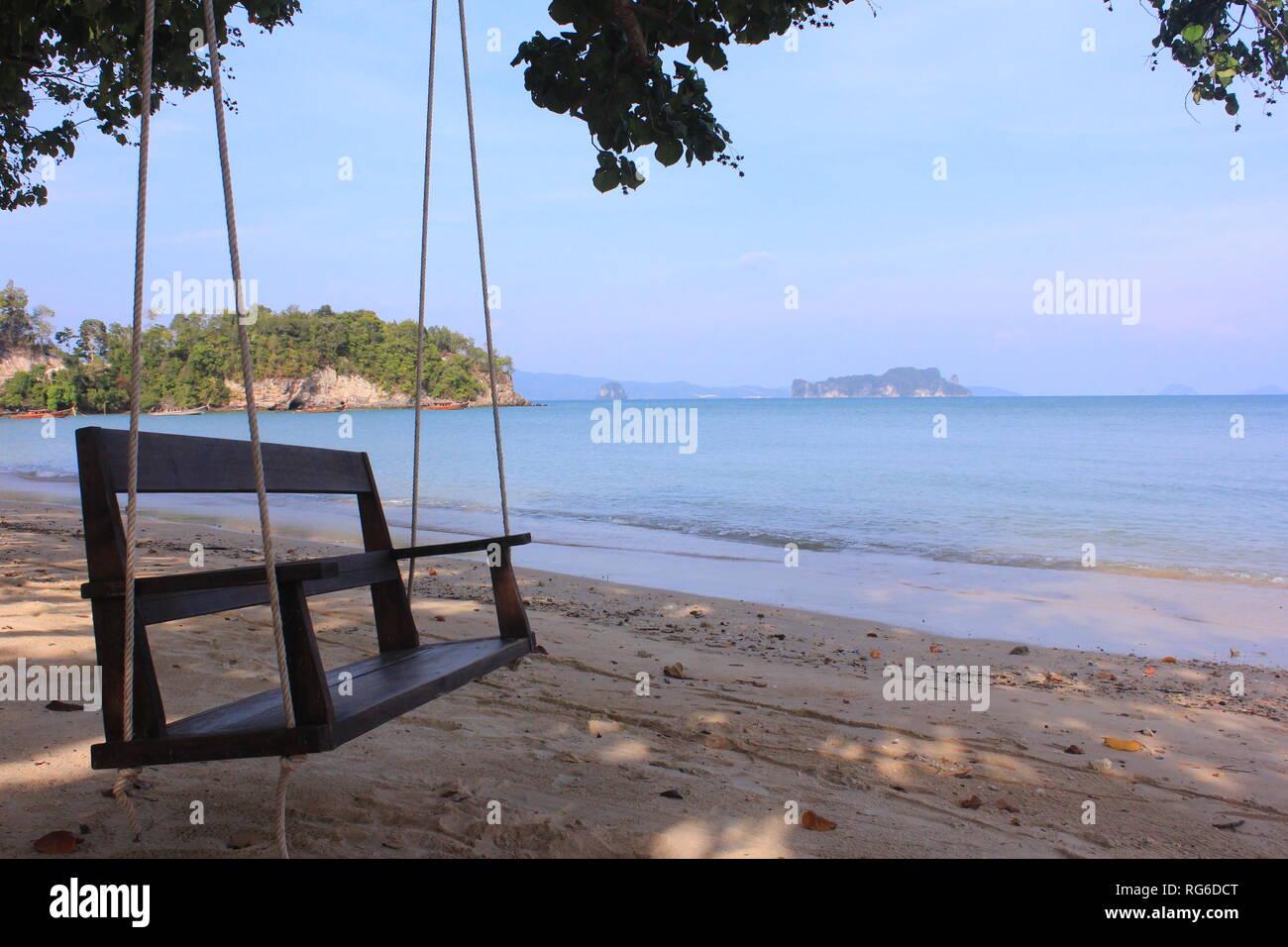 Holzschaukel am Strand einer thailändischen Insel mit Ausblick aufs Meer und die umgebenden Inseln - Stock Image